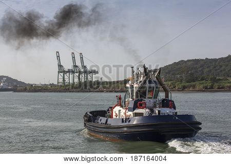 powerful Tugboat in Panama Canal, with smoke coming out of it