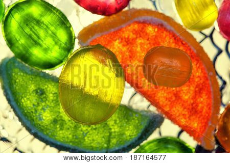 lollipops and slices of marmalade , top view. bright tropical background