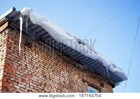 Icicles on the living house building roof.