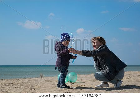 Mom with a young son in the spring on the beach playing with soap bubbles
