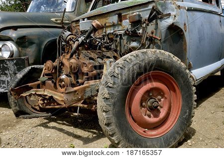 An old pickup with a V8 engine and block displays the many parts found underneath the hood of a vehicle.