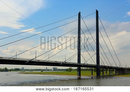 Long metal bridge above the Rhine river in Dusseldorf Germany in sunny summer day under blue sky