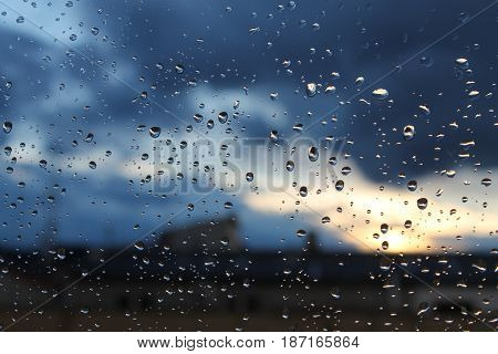 Windows with raindrops, in front of a cloudy sunset.