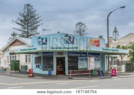 Napier New Zealand - March 9 2017: Sunshine Superette is a corner store selling groceries newspapers and basic household products. Light blue paint colored advertisement cloudy sky and street scene.