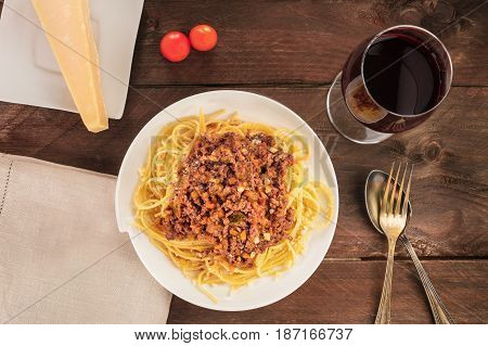 An overhead photo of a plate of spaghetti Bolognese, with meat and tomato sauce, with a glass of red wine, a slice of Parmesan cheese, cherry tomatoes, and a place for text