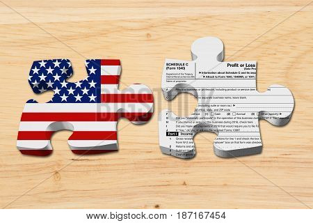 Understanding how to do your business taxes Two puzzle pieces with the flag of the USA and a US Federal tax Schedule C for 1040 income tax form on wood 3D Illustration