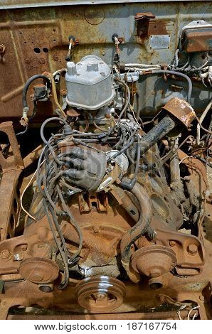 An old V8 car engine and block displays the many parts found underneath the hood of a vehicle.
