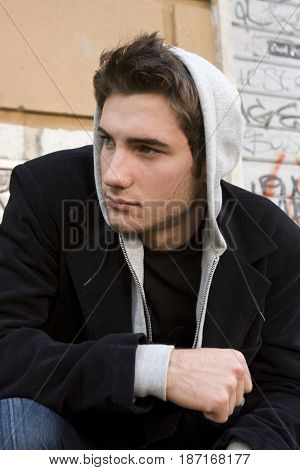 Cool handsome man model with hoodie, urban wall background. Young man with hoodie in front of a wall. Wearing a jacket, sweatshirt and dark knit.