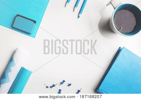 Top view of white office desktop with blue stationery items and coffee/tea mug. Copy space