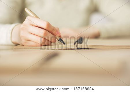 Close up of female hands writing in spiral notepad
