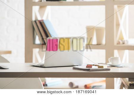 Back view of open notebook with sticker placed on modern office desktop with coffee cup supplies and other items