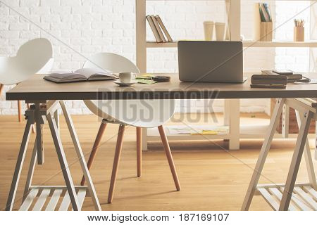 Hipster office interior with device supplies and coffee cup on table