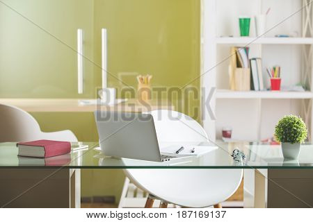 Glass table with laptop and other items in modern office. Workplace concept