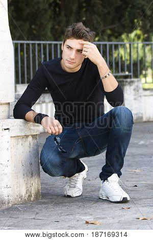 Young man concerned, sitting squatting outdoors. Thinking attitude. Modern casual clothing. Anxiety and problems. Hand in his head.