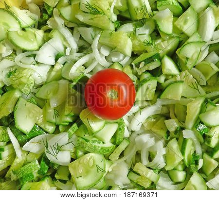Small red tomato on green cucumbers and white onion in salad. Natural food background. Vegetables texture.