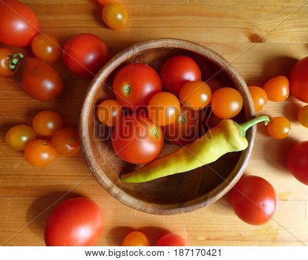 Ripe red tomatoes, cherry and hot pepper in the bowl and near it at the wooden table. Fresh organic products, pure eco food. Rural still life - new vegetables harvest. Natural ingredients, top view.
