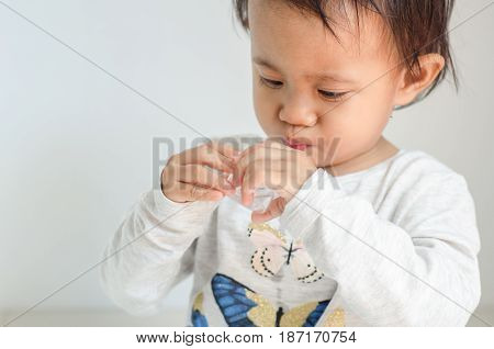 Asian little girl takes medicine syrup by herself