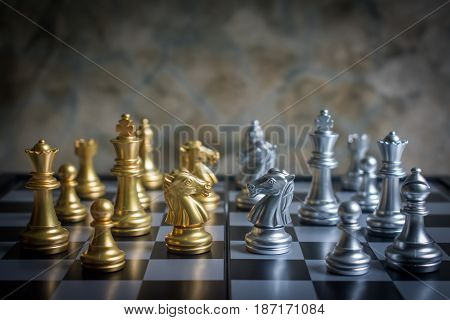 Abstract chess knights face to face on a chessboard in low key tone