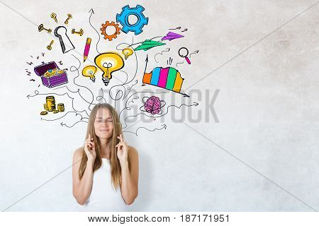 Attractive young girl with crossed fingers on concrete background with business sketch. Idea concept