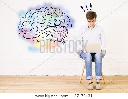 Young businessman sitting on chair and using laptop in bright interior with brain sketch on wall. Brainstorming concept
