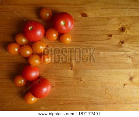 Natural background. Red ripe tomatoes and cherry at the wooden table. Fresh organic products, pure eco food. Rural still life - new vegetables harvest. With place for text.