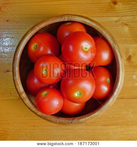Ripe red tomatoes in the bowl at the wooden table. Fresh organic products, pure eco food. Rural still life - new vegetables harvest.