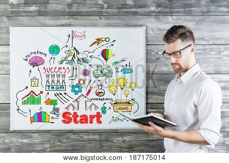Attractive young businessman reading book next to whiteboard with business sketch. Team concept. Wooden wall background