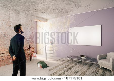 Thoughful businessman in unfinished room with blank poster ladder and furniture. Repairs concept. 3D Rendering