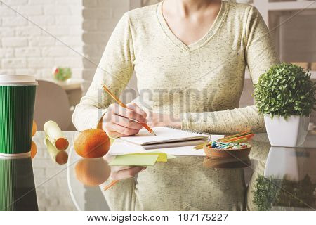 Close up of female hands writing in spiral notepad placed on office desktop with coffee cup supplies and other items. Young writer/author/artist