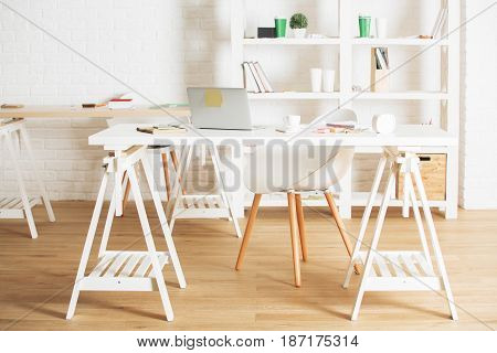 Modern office interior with device supplies and coffee cup on table