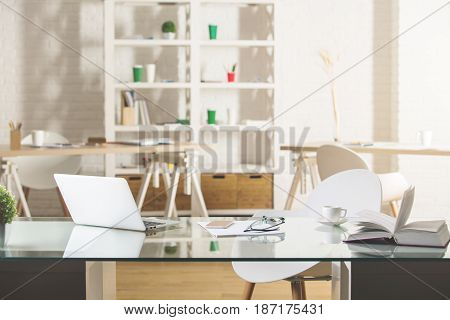 Glass desktop with laptop and other items in modern office. Workplace concept
