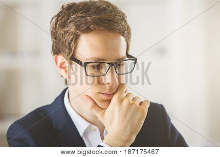 Close up portrait of thoughtful young european businessman with glasses at workplace