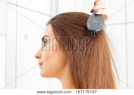 Portrait of a young girl who stands sideways in the bathroom and combs her hair closeup