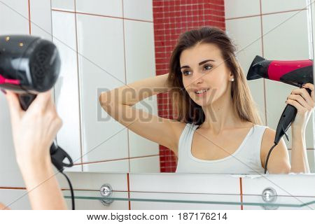 fun attractive girl stands in front of a mirror and dries long hair closeup