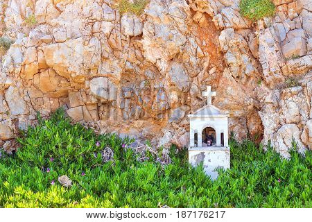Wayside chapel made of light marble with a stone cross. In the chapel of installed icons candles and incense. On background of mountain. Resort Rethymno Crete Greece