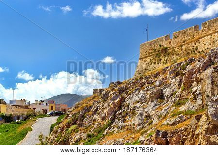 Fortezza Castle - Venetian fortress on hill Paleokastro in resort Rethymno. Greek architecture on coast of Kolpos Almirou. Greek flag flies on flagpole on tower of castle. Crete island Greece