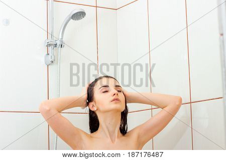young beautiful girl is standing under the shower closing her eyes and washes hands hair closeup