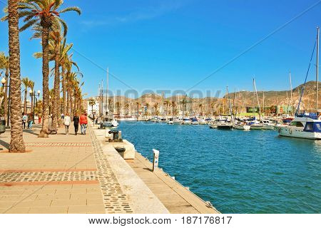 CARTAGENA, SPAIN - APRIL 30, 2016: promenade with palm trees, pier with many yachts in the bay of Cartagena city, region of Murcia.