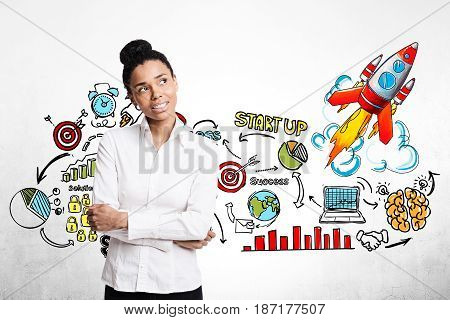 Portrait of an African American businesswoman standing with crossed arms near a concrete wall with a colorful start up sketch and rocket