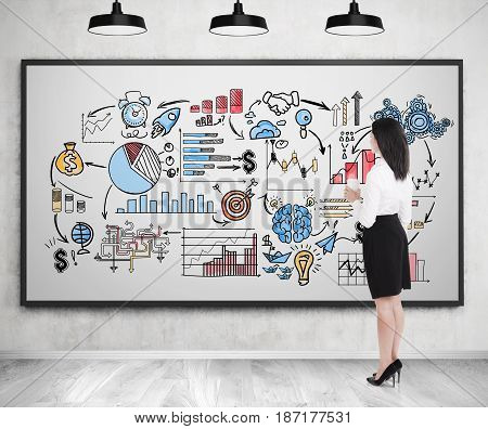 Businesswoman in a white shirt and a black skirt is holding a paper coffee cup and looking at a bright business scheme drawn on a whiteboard