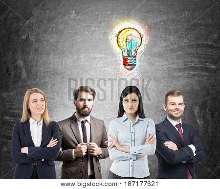 Business team consisting of two businessmen and two businesswomen is standing near a blackboard with a colorful light bulb sketch above woman s head