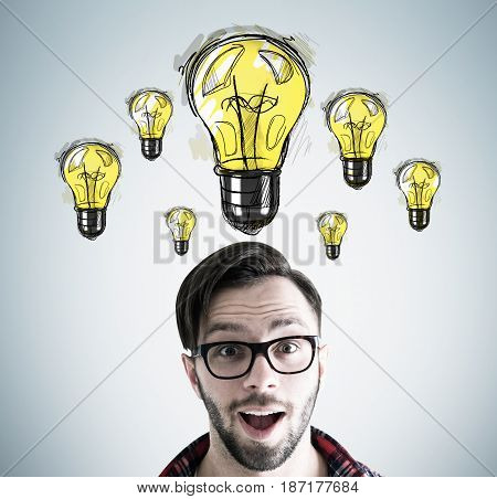 Close up of an astonished hipster guy s head with many yellow light bulbs drawn above it on a gray wall behind