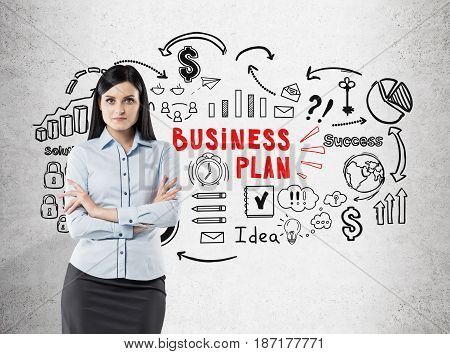 Portrait of a serious businesswoman with black hair standing with crossed arms near a concrete wall with red and black business plan icons