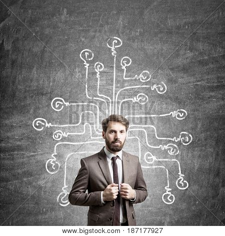 Confident young businessman in a brown suit is standing near a blackboard with a light bulb network drawn on it.