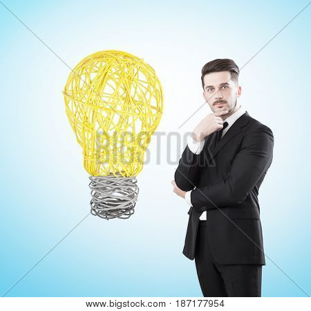 Portrait of a thoughtful bearded businessman wearing a black suit standing near a pale blue wall with a big yellow light bulb sketch to the left of him