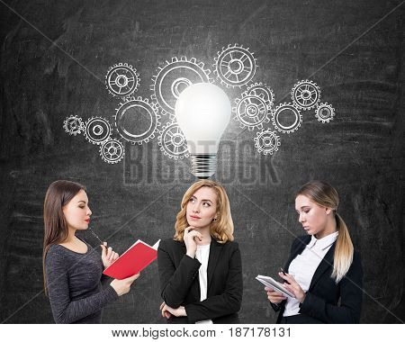 Three businesswomen are holding a book and a notebook and standing near a blackboard with glowing light bulb and many gears on it