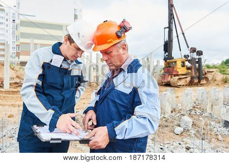 construction workers with project in front of pile driver machine