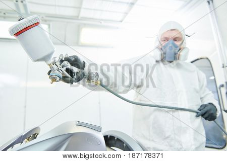 repairman painter in chamber painting automobile car bonnet
