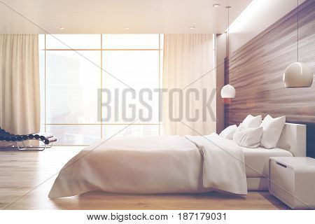 Side view of a gray wall bedroom interior with a double bed a bedside table an armchair and a large window. 3d rendering toned image