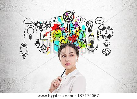 Close up of a young businesswoman holding a pen. She is standing near a concrete wall with a start up sketch and a colorful brain icon